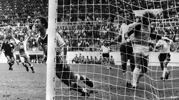 Algeria's Lakhdar Belloumi, left, turns and celebrates after scoring the second goal for his team during the Football World Cup match between Algeria and West Germany in Gijon, Spain on June 16, 1982. West Germany's goalkeeper Harald Schumacher, right, and Paul Breitner, second left, look on in dismay. Algeria defeated West Germany 2-1. (AP Photo)