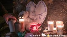 A person lights a candle at a memorial in Trier