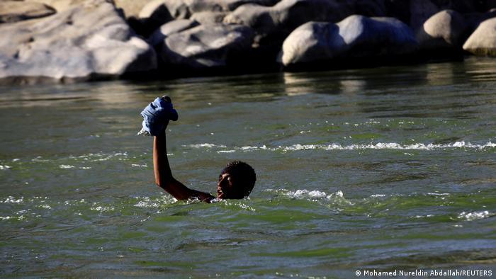 An Ethiopian crosses the Setit river on the Sudan-Ethiopia border in Hamdayet village