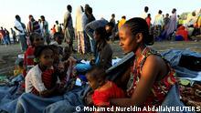 Eine aus der Region Tigray geflüchtete äthiopische Familie sitzt auf dem Boden jenseits der sudanischen Grenze