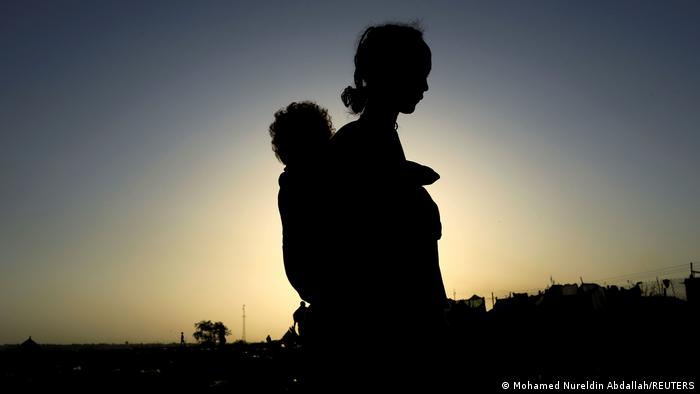 An Ethiopian woman carries her child near the Setit river on the Sudan-Ethiopia border