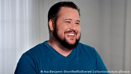 Chaz Bono, bearded and laughing in a blue sweatshirt.