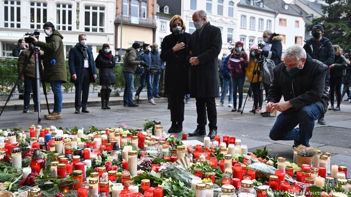 Malu Dreyer and her husband looking at the candles and flowers by the Porta Nigra, surrounded by journalists