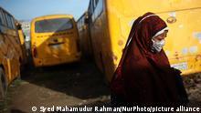 Mulher de véu e máscara protetora diante de ônibus amarelos