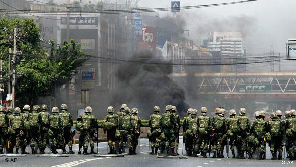Thai soldiers stand guard against some black smoke as anti-government protesters burned tires in downtown bangkok