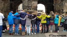 A row of people, arms entwined seen from the back, standing in front of the candles and flowers at the Porta Nigra