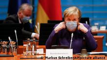 German Chancellor Angela Merkel takes down her face mask as she arrives for the weekly cabinet meeting of the German government at the chancellery in Berlin, Germany, Wednesday, Dec. 2, 2020. (AP Photo/Markus Schreiber, Pool)