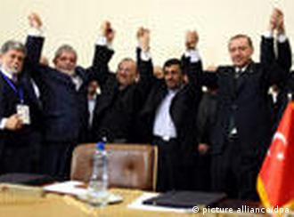 Presidents and foreign ministers of Brazil , Iran and Turkey raise their arms in unity in front of the media 17 May 2010 in Tehran , Iran , after signing an agreement to ship Iran's low enriched uranium to Turkey to exchange with nuclear fuel for a Tehran reactor.
