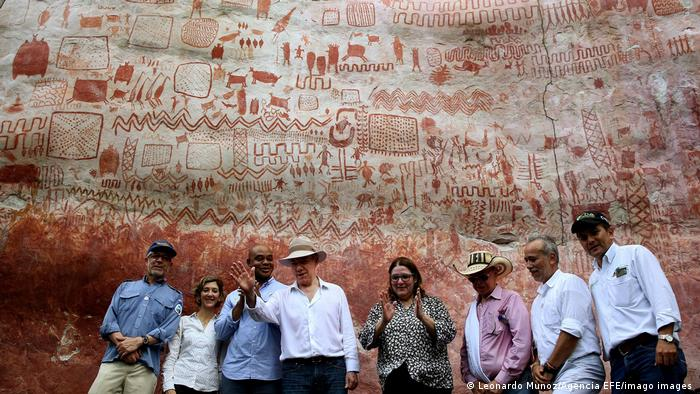 A small group of people stand below rock paintings in Chibiriquete National Park