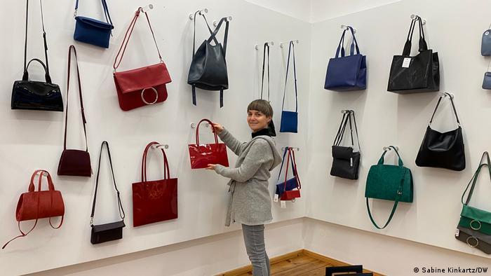 Taschendesignerin Anke Runge in ihrem Ladengeschäft vor einer Wand mit Handtaschen