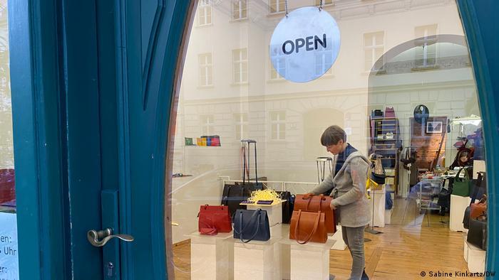 Berlin Taschenmanufaktur. Designerin Anke Runge wartet in ihrem Geschäft auf Kunden und rückt Taschen in der Auslage zurecht.