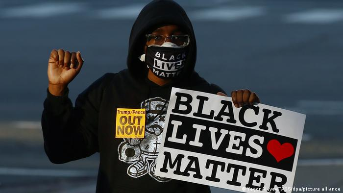 Person with a hoodie and a face mask makes a fist and holds a sign that reads Black Lives Matter
