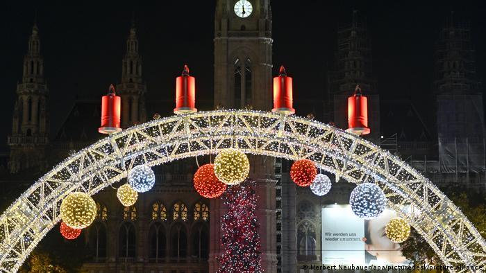 Lichterbogen mit vier Adventskerzen, im Hintergrund: Rathaus mit Weihnachtsbaum, Wien, Österreich