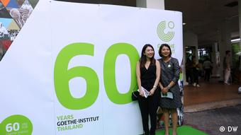 60 years Goethe Institute Thailand, two beaming guests in front of the anniversary poster