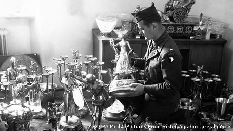 US soldier in 1945 looks at a table full of objects, holds a sculpture.