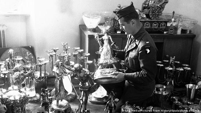 Foto em preto e branco mostra soldado americano em 1945 junto a candelabros e outras peças valiosas