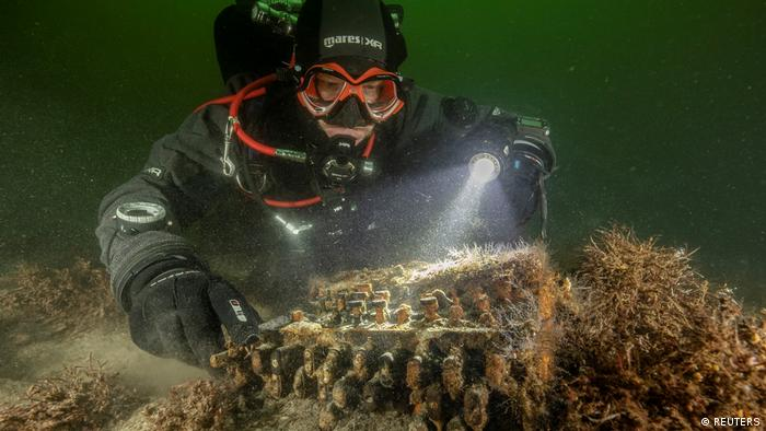 Diver and underwater archaeologist Florian Huber touches a rare Enigma cipher machine used by the Nazi military during World War Two