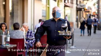 Официант в защитной маске несет поднос в кафе в калифорнийском городе Пасадена