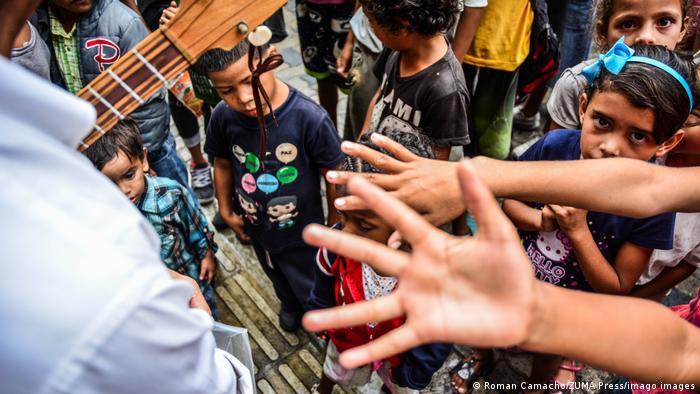 Crianças estendem braços para pegar alimentos em Caracas