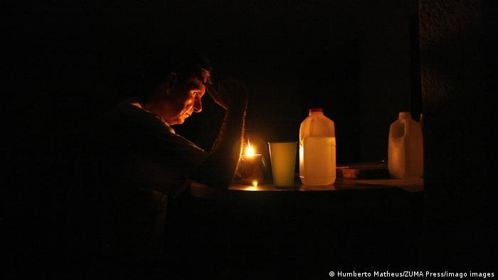 Homem sentado a luz de velas
