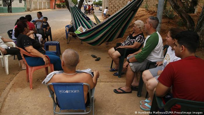 Venezuelanos conversando sentados na rua