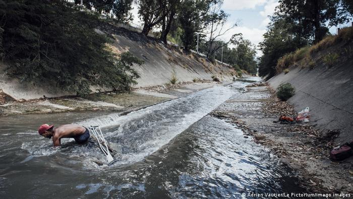 En el río Guaire solo fluyen solo aguas residuales y productos químicos tóxicos. En Venezuela, el agua y la electricidad son delicadamente interdependientes: la falta de electricidad y mantenimiento agrietaron las paredes de los embalses del país y el nivel del agua bajó. Como resultado, se generó menos electricidad en las centrales hidroeléctricas y se produjeron apagones. Un círculo vicioso.