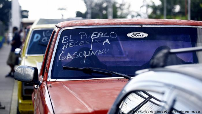 En Guacara, en el estado Carabobo, la gente espera con sus automóviles enfrente de las estaciones de servicio por más de dos semanas para cargar gasolina. Venezuela tiene que importar petróleo de Irán porque sus propias plantas petroleras en ruinas apenas pueden producir petróleo. Hace 10 años, la tasa de producción era de unos 2,3 millones de barriles al día. Ahora es menos de la mitad.