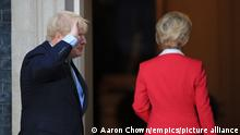 Boris Johnson raises his hand in salute next to Ursula von der Leyen