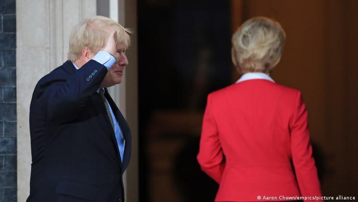 Boris Johnson raises his hand in salute next to Ursula von der Leyen