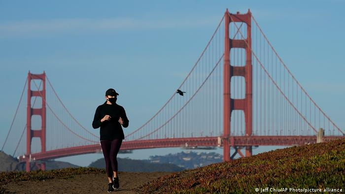 A woman wearing a face mask is jogging before the background of the Golden Gate Bridge