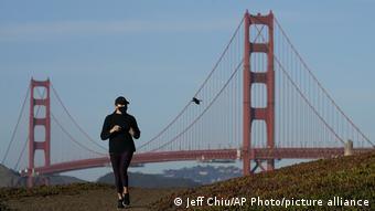 Женщина в маске занимается бегом на фоне моста Золотые ворота