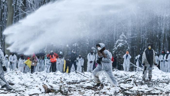 Manifestante corre em meio à neve e chuva de jato de água