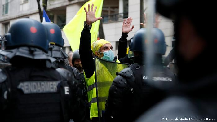 A protester wearing a yellow vest holds up his hands during a demonstration against a new security law in Paris