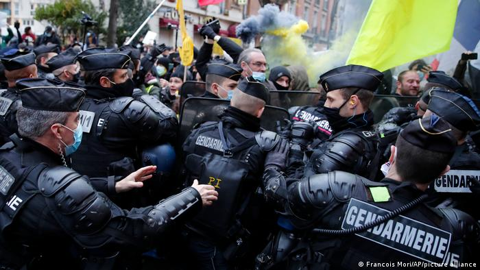 Protesters are blocked by riot police officers during a demonstration in Paris, France
