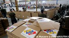 People work by the boxes for voting materials at the National Electoral Council facility in Guarenas, Venezuela November 27, 2020. Picture taken November 27, 2020. REUTERS/Manaure Quintero