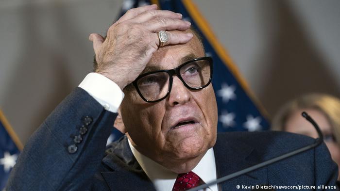 Giuliani, de terno escuro e gravata vermelha, com a mão esquerda na cabeça.
