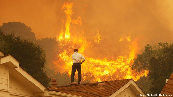 A man stands on the roof of a house looking a raging wildfire.
