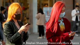 Женщины в защитных масках смотрят на экраны смартфонов