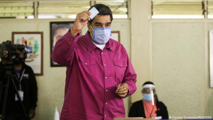 Nicolás Maduro, con mascarilla, deposita su voto en los comicios parlamentarios.