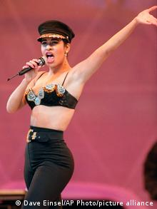 Selena Quintanilla dancing and singing onstage with a black outfit and hat