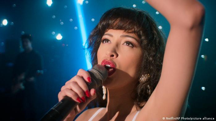 Junge Frau mit Trägertop und roten, langen Fingernägel singt in ein Mikrofon.