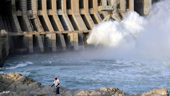 A Sudanese man walks in front of the Merowe hydroelectric dam