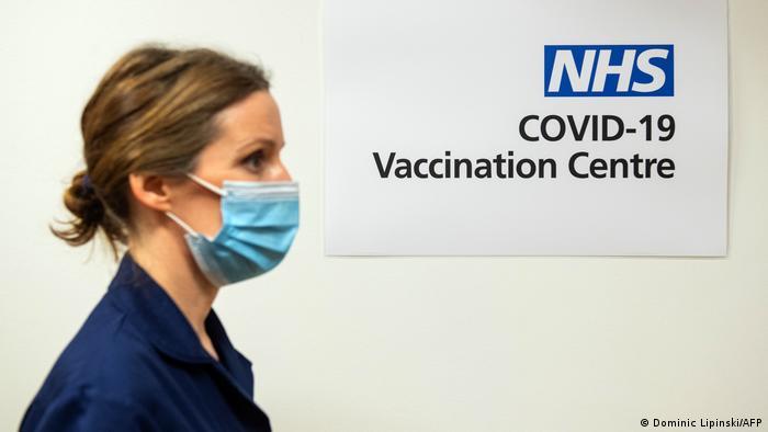 Mulher caminha usando máscara em frente a placa do NHS indicando centro de vacinação