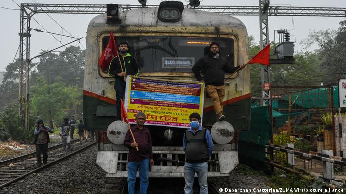 Men block a train in Kolkata