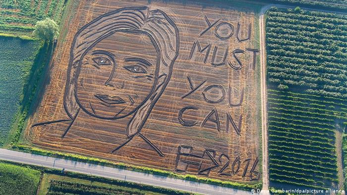 Aerial view of a land art portrait of Hillary Clinton with the words 'You must, you can.'