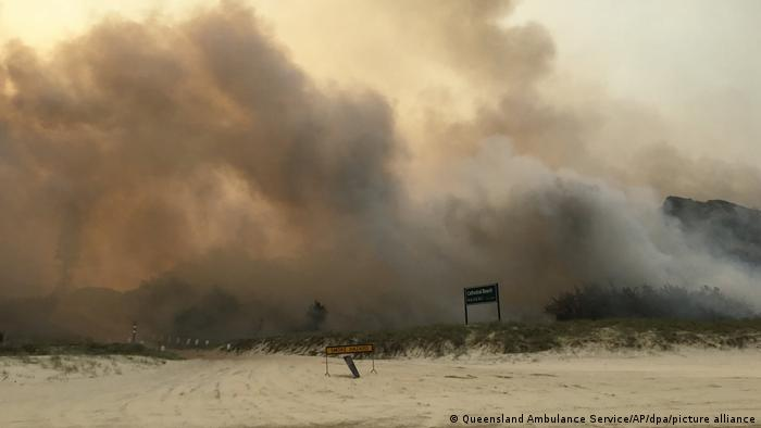 Clouds of smoke from a fire sweep across a beach