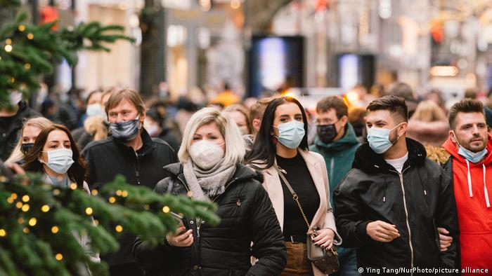 Shoppers in Cologne wear masks