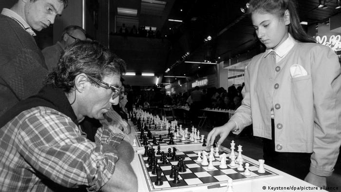 Judit Polgár stands at a chess board and moves a piece with an older man playing against her
