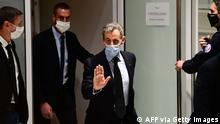 Former French President Nicolas Sarkozy (C) leaves after a hearing at his trial on corruption charges on December 8, 2020 at Paris courthouse. - Prosecutors in the graft trial of French ex-president Nicolas Sarkozy on December 8, 2020 called for him to be sentenced to a prison term of four years, two of which should be suspended. The 65-year-old rightwinger, the country's first modern head of state to appear in the dock, is accused of trying to bribe a judge with a plum retirement job in exchange for inside information on an inquiry into his campaign finances. (Photo by Martin BUREAU / AFP) (Photo by MARTIN BUREAU/AFP via Getty Images)