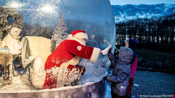 Papá Noel en una burbuja de aire saludo a niños.